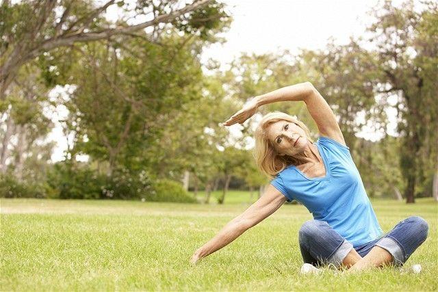 únik moču - žena - cvičenie - trávnik - voľný čas - slnko - jóga
