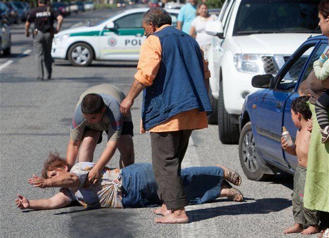 Na snímke leží na zemi matka jedného zo zavraždených.