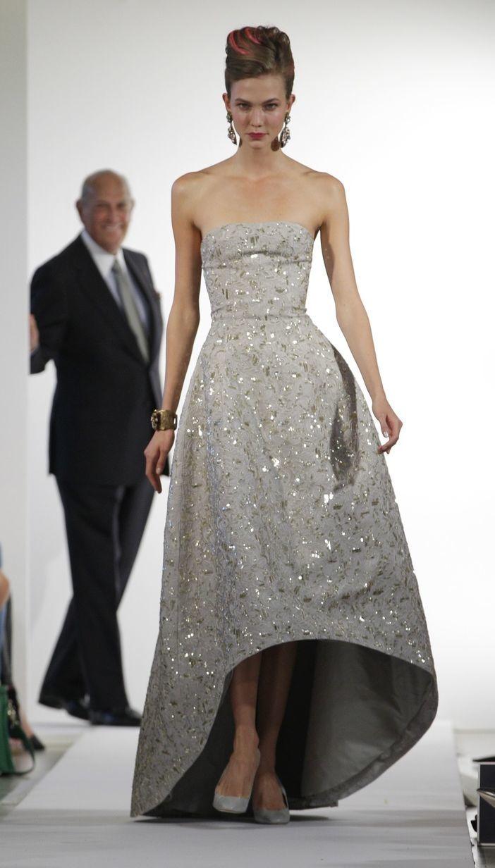 Modelka Karlie Kloss v róbe od Oscara de la Rentu (na snímke v pozadí) v róbe, ktorá uzatvárala prehliadku jarnej kolekcie 2013.