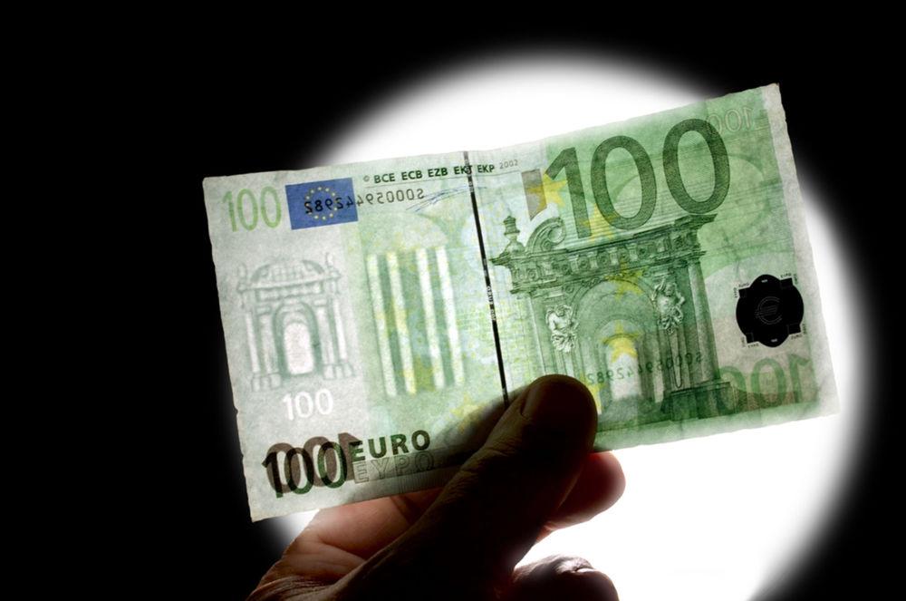 Kontrola vodotlače na stoeurovej bankovke pod UV lampou s bielym svetlom.