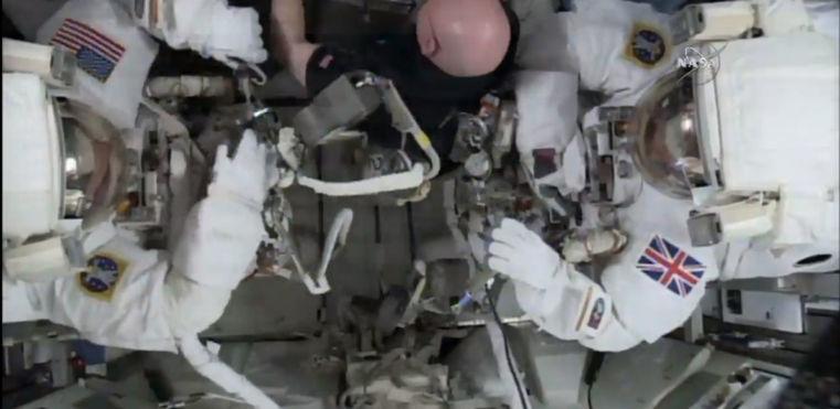 Fotografia z videa NASA zachytáva výstup astronautov Tima Kopru, Tima Peaka a Scotta Kellyho mimo stanicu ISS.