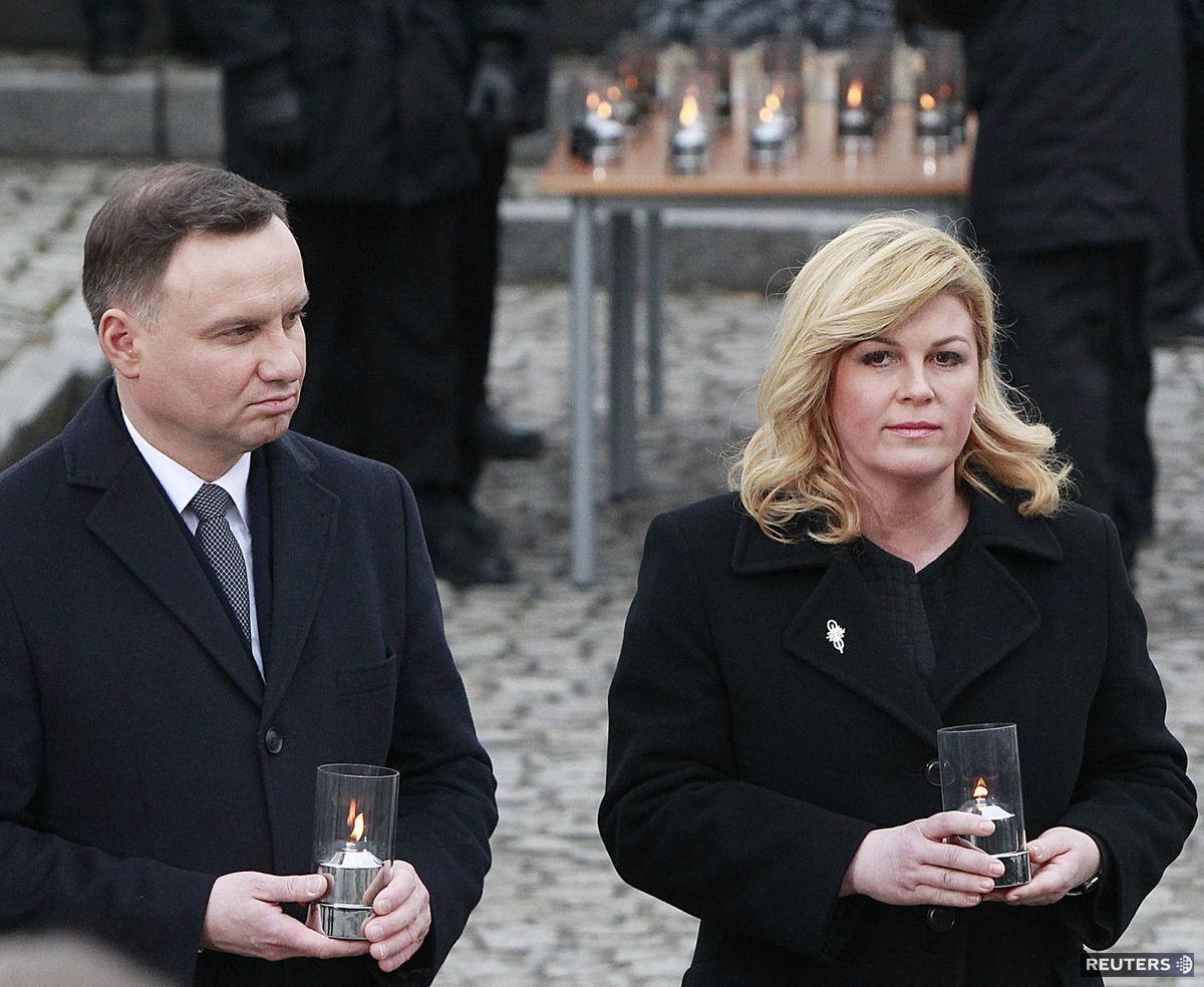 Chorvátska prezidentka Kolinda Grabarová-Kitarovičová a poľský prezident Andrzej Duda zapaľujú sviečky počas slávnostnej ceremónie v tábore Auschwitz v Osvienčime.