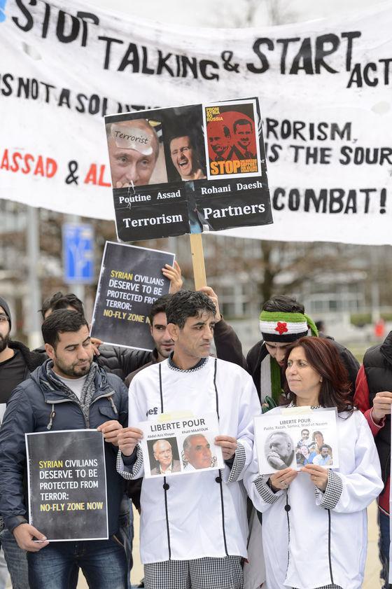 V Ženeve, kde sa začali mierové rokovania o Sýrii, demonštranti držia transparenty odsudzujúce režim Bašára Asada.