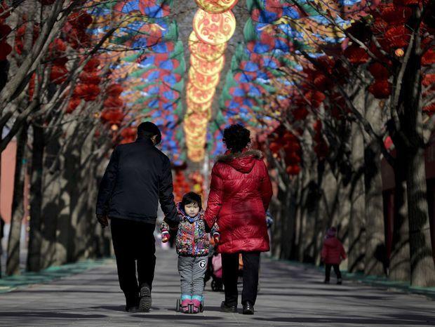 Čínska rodinka - dieťa na skútri. Prechádzajú sa popod dekorácie pripravené pred príchodom čínskeho lunárneho nového roka v parku Ditan v Pekingu. Číňania privítajú nový rok 8. februára a nastane rok opice.