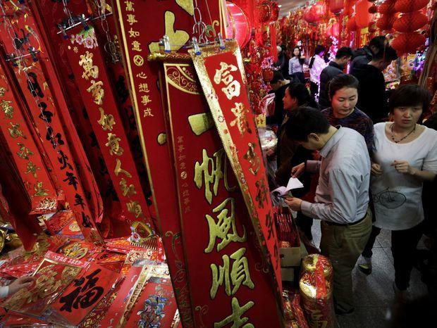 Číňania nakupujú dekorácie pred oslavami čínskeho nového lunárneho roka na trhovisku v Pekingu.