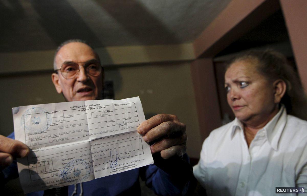 Kubánsky disident Hector Maseda stojí vedľa svojej ženy a ukazuje prepustenie z väzenia.