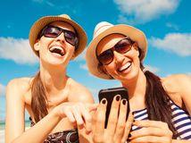 leto, dovolenka, cestovanie, more, mobil, smartfón, smiech, kamarátky, sestry, slnečné okuliare, plavky, opaľovanie, slnko, slnenie