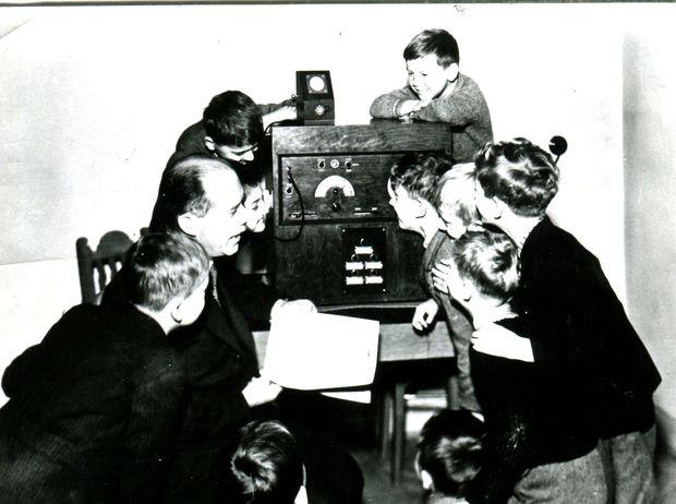 Žiaci v 30. rokoch počúvajú rozhlasové vysielanie pre školy.