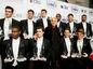 Televízna osobnosť Ellen DeGeneres (v strede) pózuje s mladými fešákmi, ktorí rozdávali ceny People´s Choice Awards.