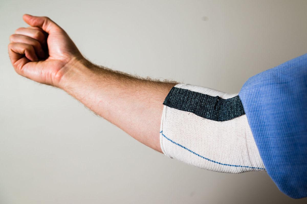 Elastický obväz vybavený novým materiálom, ktorý pomáha pri pohybe lakťom.