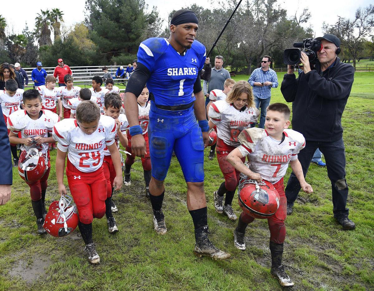 Hráč amerického futbalu Cam Newton počas nakrúcania reklamy pre automobilku Buick s detskými hercami.
