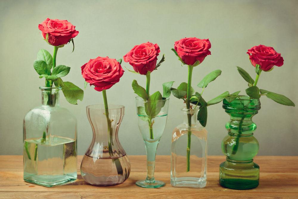 Stačí zopár červených ruží s krátkymi stopkami a tie môžete takto efektne aranžovať v skvelených fľačiach na komode či na stole.