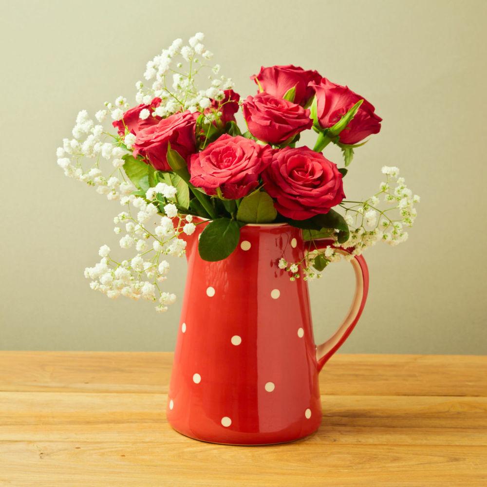 Nežná romantika, o ktorú sa postarajú červené ruže v bodkovanom džbáne. Jemnosť ešte zvýraznia drobné biele kvietky v červenej kytici.