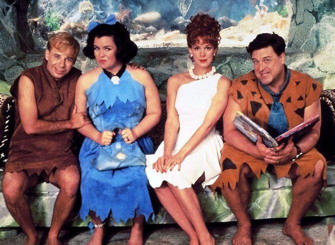 Rick Moranisová, Rosie O'Donnell, Elizabeth Perkinsová a John Goodman vo filme Flintstonovci (1994).