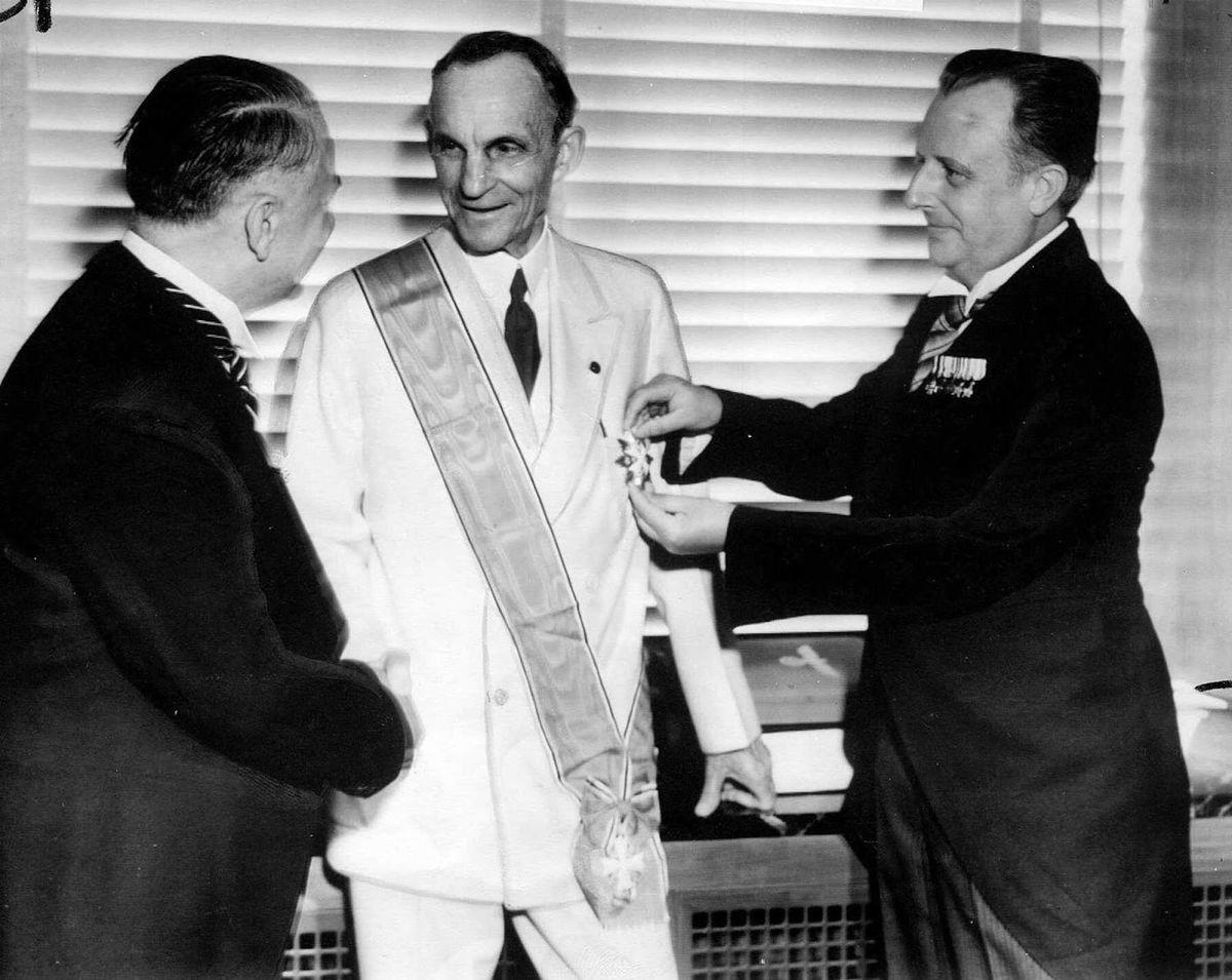 Henry Ford mal blízko k Adolfovi Hitlerovi. Na snímke z apríla  1938 preberá v meste Deabor (štát Michigan) pri príležitosti svojich 75. narodenín najvyššie vyznamenanie nacistického Nemecka  udeľované cudzincovi Veľkokríž radu Nemeckého orla.