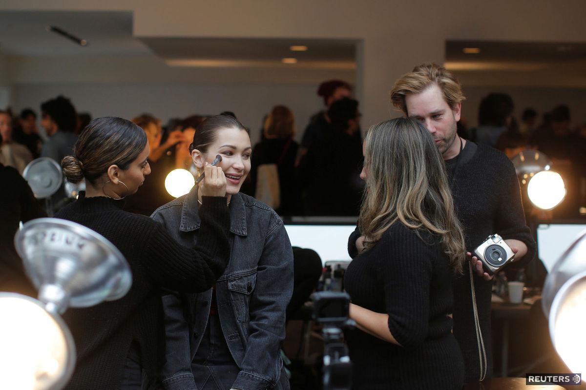 Modelka Bella Hadid sa pripravuje na prehliadku Michaela Korsa  v New Yorku. Základ je líčenie. Okolo modelky sa motá celý tím ľudí. Kým jeden človek upravuje tvár, druhý často simultánne pracuje na manikúre alebo na účese. Hadid občas živo konverzuje s celým tímom a niekedy si založí slúchadlá a počúva hudbu. Berie to ako rutinu, tvrdia ľudia z módnej brandže.