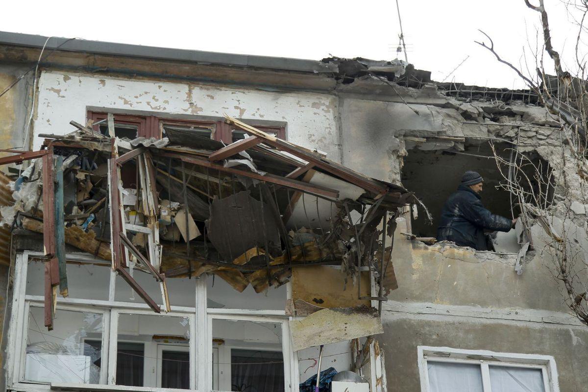 Pracovník miestnej samosprávy kontroluje škody na dome po ostreľovaní centra Donecka ukrajinskou armádou.