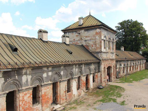 Výhľad na ošarpanú budovu a nádvorie zo zrekonštruovanej kaplnky.