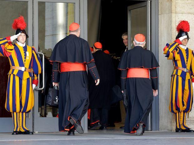 Členovia švajčiarskej gardy pozdravujú kardinálov.