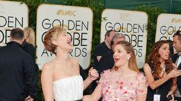 Herečky Jennifer Lawrence, (vľavo) a Drew Barrymore sa zdravia na červenom koberci.