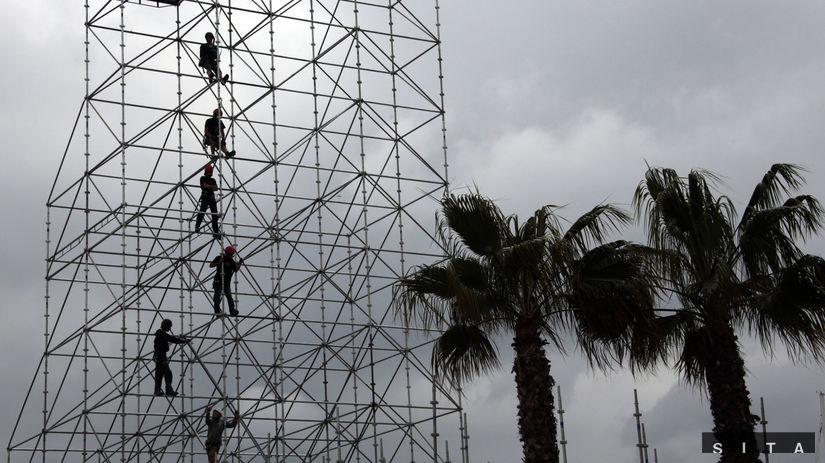 Siluety robotníkov pri stavaní lešenia v...