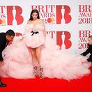 Asistenti pomáhajú speváčke Dua Lipa s jej masívnymi šatami.