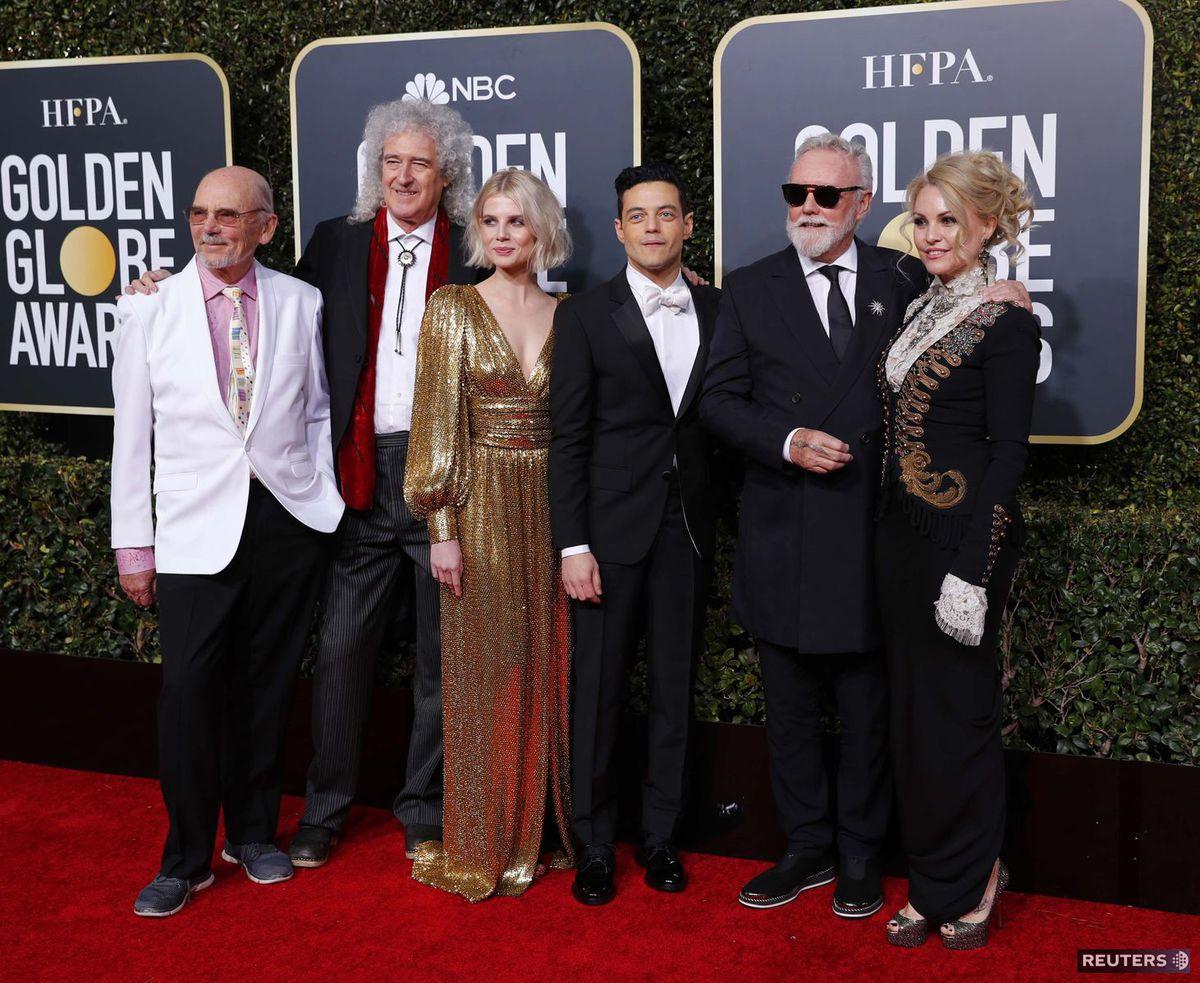 Hudobníci a členovia formácie Queen John Deacon (vľavo), Brian May (druhý zľava) a Roger Taylor (vpravo s partnerkou) pózujú s hercami z víťazného filmu Bohemian Rhapsody - Lucy Boyntonovou a Rami Malekom, ktorý stvárnil Freddieho Mercuryho.