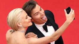 Snúbenci Pixie Lott a Oliver Chesire si robia selfie na červenom koberci.