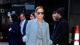 Speváčka Jennifer Lopez v kreácii trblietavého overalu a kabáta lemovaného perím v identickom odtieni.