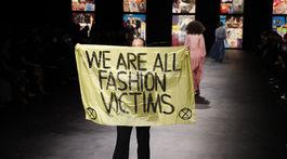 Aktivistka na prehliadke značky Dior s transparentom Všetci sme obete módy.