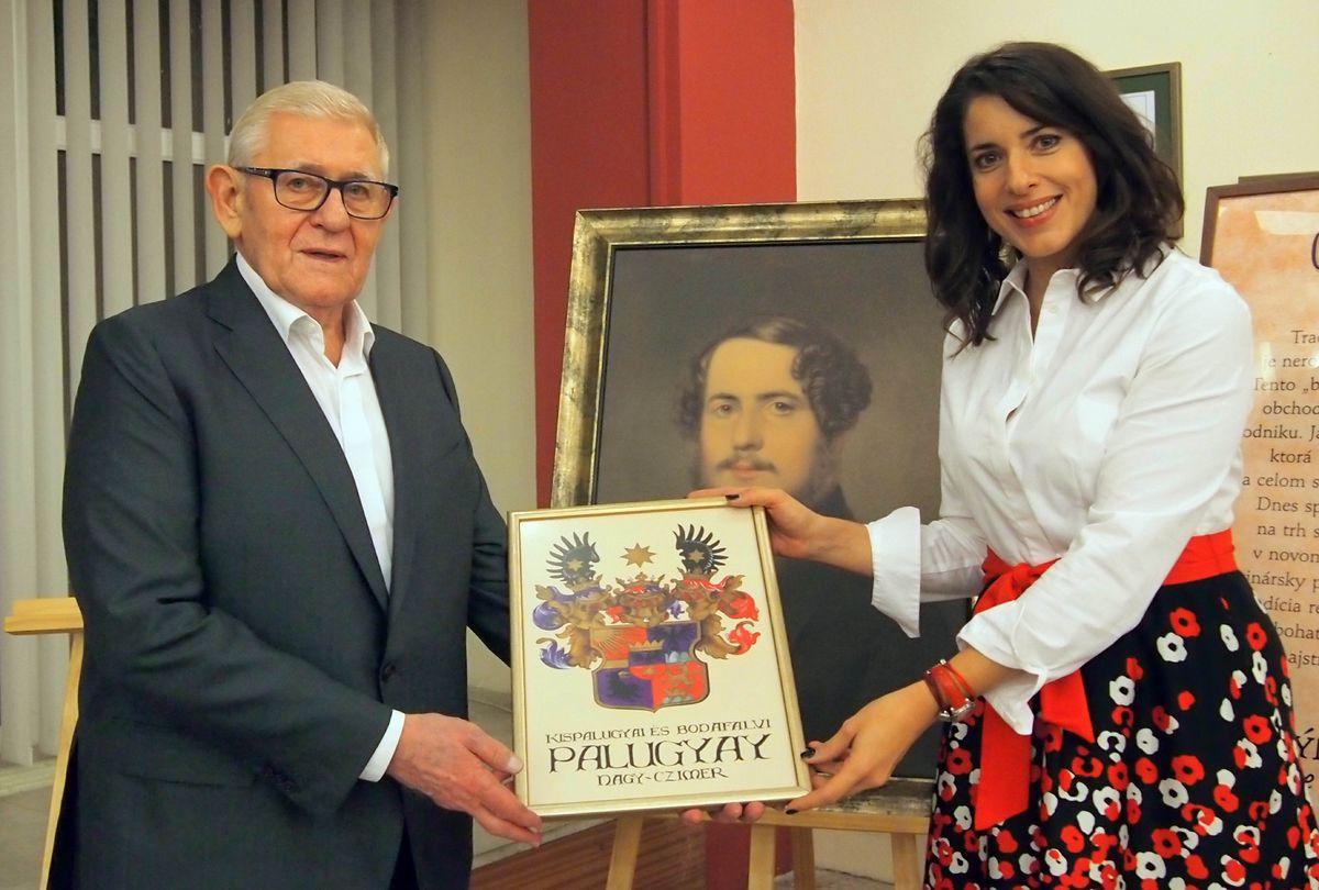 Prapravnučka Jakuba Palugyaya odovzdáva generálnemu riaditeľovi Villa Vino Rača Jánovi Kramplovi rodový erb Palugyayovcov.