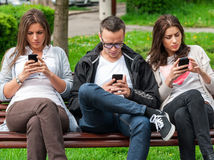 Group of friends two women and one man, sitting on a bench in park separately looking at their phones loosing communication. people using their phones and sending texts as they stand beside each other