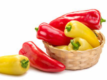 red and yellow pointed paprika in a basket. Isolate on white background