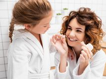Smiling woman holding dental floss near teeth and daughter in bathroom